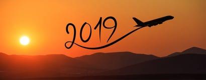 Año Nuevo 2019 volando el aeroplano en el aire en la salida del sol, bandera Fotos de archivo