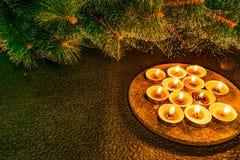 Año Nuevo y la Navidad, pino artificial verde en un fondo negro teniendo en cuenta velas de la cera Tactos acogedores calientes a imágenes de archivo libres de regalías
