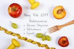Año Nuevo y resoluciones de la inscripción polaca, frutas, pesas de gimnasia y centímetro Foto de archivo libre de regalías