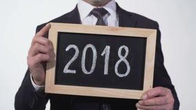 Año 2017, 2018, secuencia 2019 en la pizarra en manos del hombre de negocios, informe anual almacen de metraje de vídeo