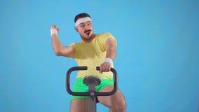 Años 80 útiles del atleta con un bigote en una bicicleta estática en un fondo azul MES lento almacen de video