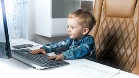 2 años adorables del niño pequeño que usa el ordenador en oficina Concepto de niños elegantes Imágenes de archivo libres de regalías