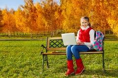 11 años agradables de la muchacha con el ordenador portátil Fotografía de archivo