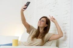 30 años atractivos de la mujer que juega en el sofá casero del sofá que toma el retrato del selfie con el teléfono móvil Foto de archivo libre de regalías
