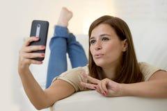 30 años atractivos de la mujer que juega en el sofá casero del sofá que toma el retrato del selfie con el teléfono móvil Fotografía de archivo