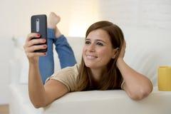 30 años atractivos de la mujer que juega en el sofá casero del sofá que toma el retrato del selfie con el teléfono móvil Imagenes de archivo