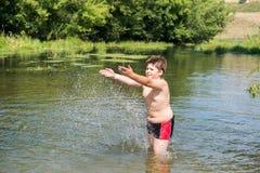 10 años completos de nadada del muchacho en el río Fotografía de archivo libre de regalías