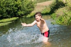 10 años completos de nadada del muchacho en el río Imágenes de archivo libres de regalías