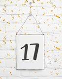 17 años de cumpleaños de la tarjeta de la fiesta con el número diecisiete con oro Foto de archivo