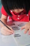 3 años de la muchacha asiática dibujan y los sketchs muchos rostros humanos con p Foto de archivo