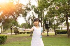 7 años de la muchacha asiática gozan con las burbujas de jabón en parque Imagenes de archivo