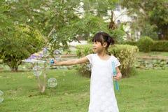 7 años de la muchacha asiática gozan con las burbujas de jabón en parque Fotos de archivo