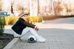 10 años de la muchacha con el uno mismo que equilibra el monopatín eléctrico Foto de archivo