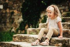 5 años de la muchacha del niño que se sienta en las escaleras de piedra viejas Imagen de archivo libre de regalías