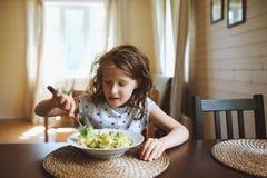 8 años de la muchacha feliz del niño que come las pastas en casa Imágenes de archivo libres de regalías