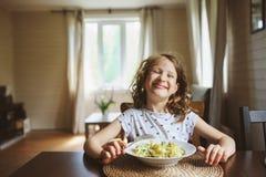 8 años de la muchacha feliz del niño que come las pastas en casa Imagenes de archivo