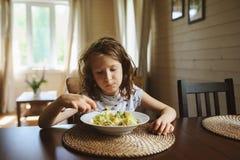 8 años de la muchacha feliz del niño que come las pastas en casa Fotos de archivo libres de regalías