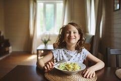 8 años de la muchacha feliz del niño que come las pastas en casa Fotos de archivo