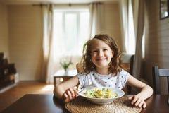 8 años de la muchacha feliz del niño que come las pastas en casa para el almuerzo Fotografía de archivo libre de regalías