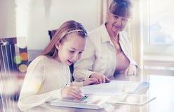 10 años de la muchacha y su profesor Estudio de la niña durante su lección privada Concepto preceptoral y educativo Imágenes de archivo libres de regalías