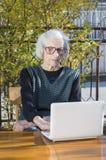 90 años de la mujer que tiene una llamada video Imagen de archivo libre de regalías