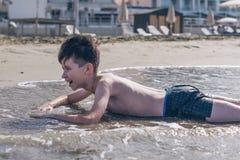13 años de la natación y relajación del muchacho en las ondas del mar imagen de archivo libre de regalías