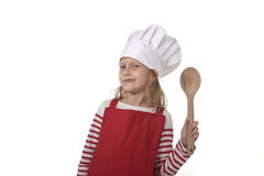 7 años de la niña en cocinar el sombrero y el delantal rojo que juegan la cuchara que se sostiene feliz sonriente del cocinero Foto de archivo libre de regalías