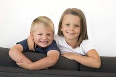 7 años de la niña hermosa que presenta en casa el sofá feliz del sofá con sus pequeños jóvenes lindos 3 años del hermano en herma Imagen de archivo