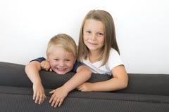 7 años de la niña hermosa que presenta en casa el sofá feliz del sofá con sus pequeños jóvenes lindos 3 años del hermano en herma Foto de archivo libre de regalías