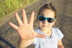 5 años de la niña muestran cinco fingeres Foto de archivo