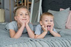 7 años de la niña que juega en cama o el sofá así como sus 3 años de la pequeña sonrisa del hermano feliz Imagenes de archivo
