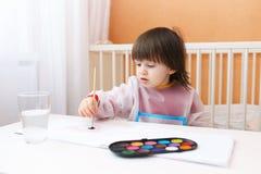 2 años de muchacho con color del cepillo y de agua pintan en casa Imagen de archivo libre de regalías