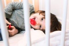 2 años de muchacho con el maniquí en la cama blanca Fotografía de archivo libre de regalías