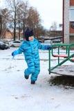 5 años de muchacho en el guardapolvo caliente que juega al aire libre en invierno Fotos de archivo libres de regalías