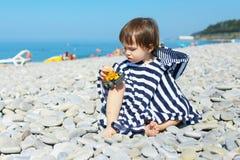 2 años de muchacho en la manta rayada que se sienta en los guijarros varan y Imagen de archivo libre de regalías