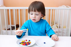 2 años de muchacho juegan con las tenazas y las gotas en casa Imagen de archivo