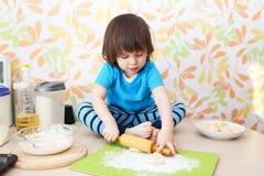 2 años de muchacho que aplana la pasta que se sienta en una tabla Imágenes de archivo libres de regalías