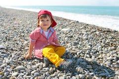 2 años de muchacho que se sienta en la playa Fotos de archivo