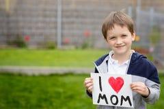 7 años de muchacho que sostiene una tarjeta de felicitación para su madre Foto de archivo libre de regalías