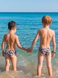 6-7 años de muchachos delante del mar de común acuerdo Imagen de archivo libre de regalías