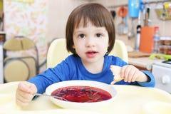 2 años de niño comen el borsch Imagenes de archivo