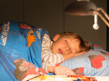 8 años de niño durmiente en la cama; dormitorio Foto de archivo libre de regalías