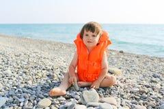 2 años de niño en la chaqueta salvavidas que se sienta en la playa Fotos de archivo libres de regalías