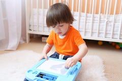 2 años de niño en pinturas anaranjadas de la camiseta en la tableta magnética en el hom Foto de archivo libre de regalías