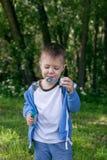 4 años de niño pequeño con las burbujas de jabón en árboles del verde del verano parquean, tiempo libre divertido Muchacho en las Imágenes de archivo libres de regalías