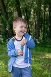 4 años de niño pequeño con las burbujas de jabón en árboles del verde del verano parquean, tiempo libre divertido Muchacho en las Foto de archivo libre de regalías