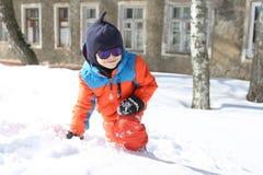 5 años de niño pequeño en el traje de esquí anaranjado caliente que juega al aire libre en w Imagen de archivo libre de regalías