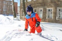 5 años de niño pequeño en el traje de esquí caliente que juega al aire libre en nieve Imagenes de archivo