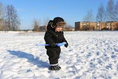 2 años de niño pequeño que camina con la pala en invierno Foto de archivo libre de regalías