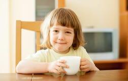 2 años de niño que bebe de la taza Imagen de archivo